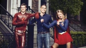 Left to right: Barry Allen/The Flash (Grant Gustin), producer Greg Berlanti, Kara Danvers/Supergirl (Melissa Benoist)